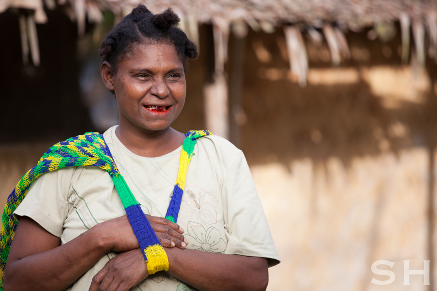 A beautiful Papua New Guinean woman that is chewing betel nut which dyes your mouth red.